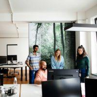 Gruppe von Mitarbeiter:innen am Computer